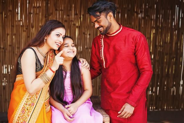 Szczęśliwa indyjska rodzina wskazująca na coś palcem