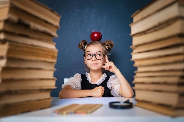 Szczęśliwa inteligentna dziewczyna w zaokrąglonych okularach w zamyśleniu siedzi między dwoma stosami książek z czerwonym jabłkiem na głowie