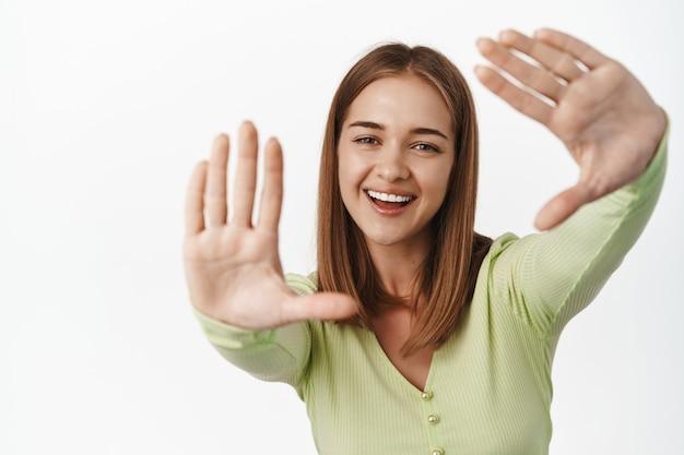 Szczęśliwa jasna młoda kobieta śmiejąca się, uśmiechająca się i patrząca przez ramki ręczne, obrazująca coś