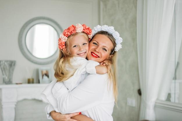 Szczęśliwa jasnowłosa mama i śliczna córka w wieńcach z kwiatami w pokoju dziennym, szczęśliwy rodzinny styl życia