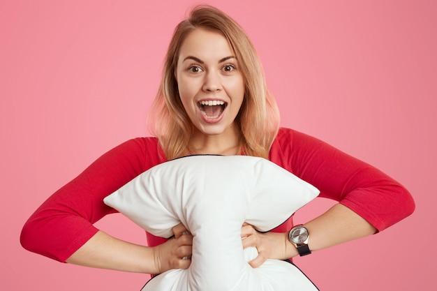 Szczęśliwa jasnowłosa młoda kobieta z rozradowanym wyrazem twarzy, trzyma miękką białą poduszkę, szeroko otwiera usta