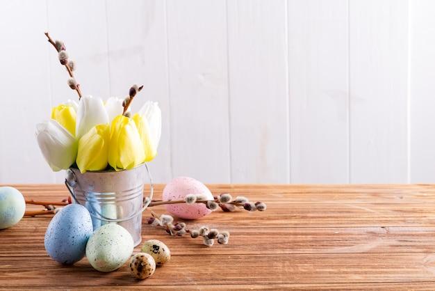 Szczęśliwa kartka wielkanocna z świeżych wiosennych tulipanów kwiatów w wiadrze i ręcznie malowane jajka na drewnianym stole.