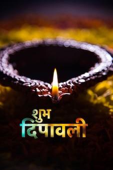 Szczęśliwa kartka z życzeniami diwali wykonana przy użyciu tradycyjnej indyjskiej glinianej lampy umieszczonej nad rangoli płatków nagietka, z bliska i selektywna ostrość
