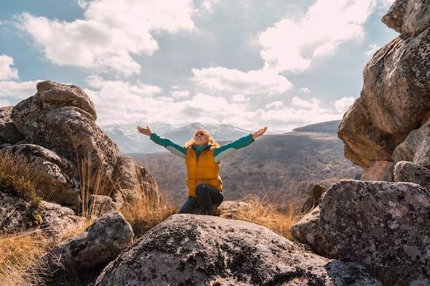 Szczęśliwa kaukaska kobieta ciesząca się przyrodą w górach