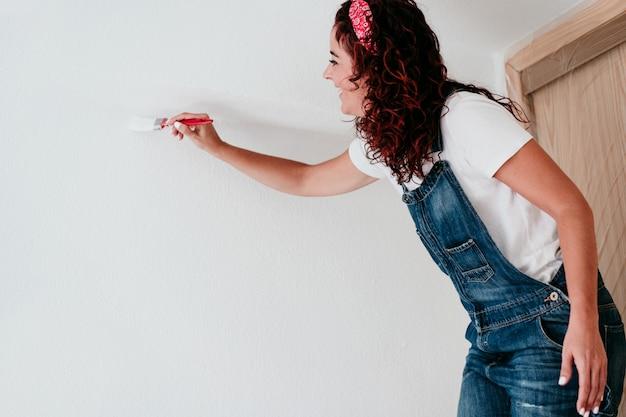 Szczęśliwa kaukaska kobieta maluje ściany pokoju białym kolorem. zrób to sam i nowa koncepcja domu