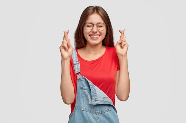 Szczęśliwa kaukaska kobieta o ciemnych włosach, trzyma kciuki, modli się o szczęście, marzy o spełnieniu marzeń, ma szeroki uśmiech