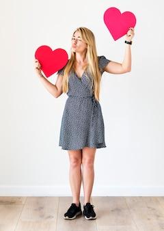 Szczęśliwa kaukaska kobieta trzyma czerwonych serca