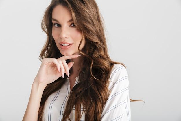 Szczęśliwa kaukaska kobieta uśmiecha się i patrzy na kamerę odizolowaną na białym tle