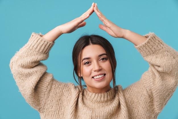 Szczęśliwa kaukaska kobieta uśmiecha się i pokazuje znak domu na białym tle nad niebieską ścianą