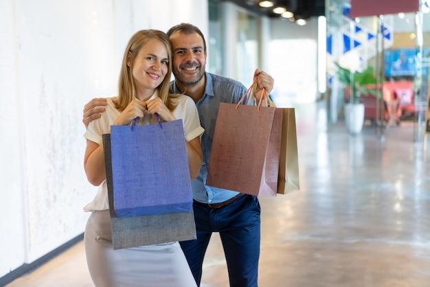 Szczęśliwa kaukaska para robi zakupy w ujścia centrum handlowym.