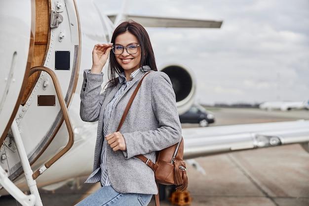 Szczęśliwa kaukaska piękna bizneswoman o ciemnych włosach wsiada do prywatnego odrzutowca