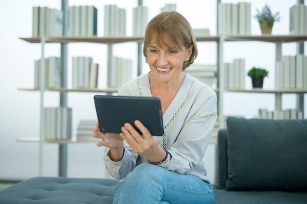 Szczęśliwa kaukaska starsza kobieta wideorozmowa z rodziną lub przyjaciółmi, relaks w domu, uśmiechnięci zdrowi starsi emerytowani dziadkowie, starsza koncepcja technologii dziadków