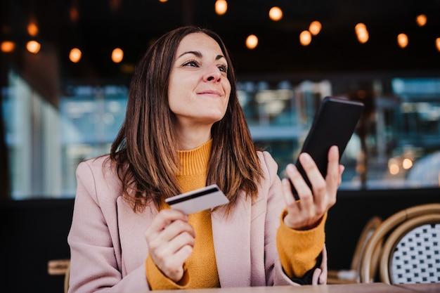 Szczęśliwa kaukaski kobieta na tarasie przy użyciu telefonu komórkowego i karty kredytowej na zakupy online. koncepcja technologii i stylu życia