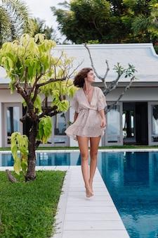 Szczęśliwa kaukaski kobieta w krótkiej letniej sukience poza hotelem willowym przy drzewie i niebieskim basenie