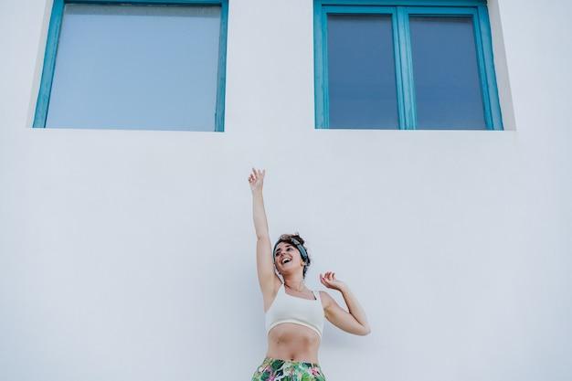 Szczęśliwa kaukaski kobieta z podniesionymi rękami przed niebieskimi oknami i białą ścianą w okresie letnim. styl życia na zewnątrz