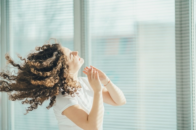 Szczęśliwa kędzierzawa kobieta słuchająca muzyki przy oknie
