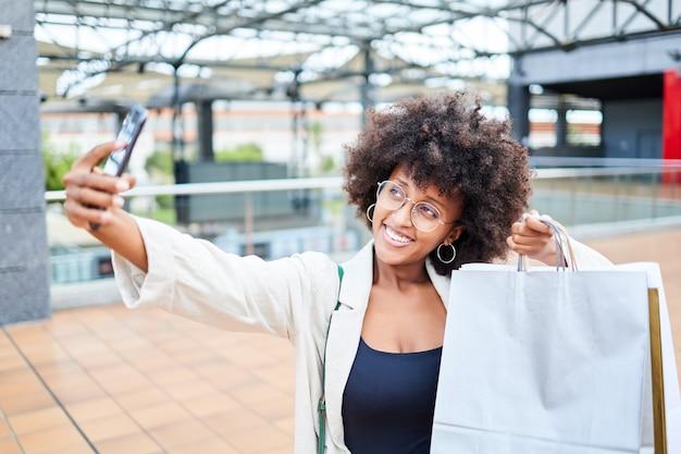 Szczęśliwa kobieta afro robi selfie podczas zakupów