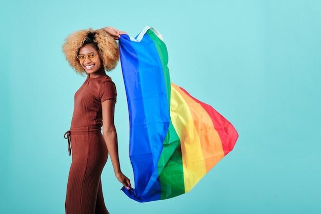 Szczęśliwa kobieta afro trzymająca flagę dumy lgbt, stojąc na na białym tle. koncepcja społeczności lgbt.