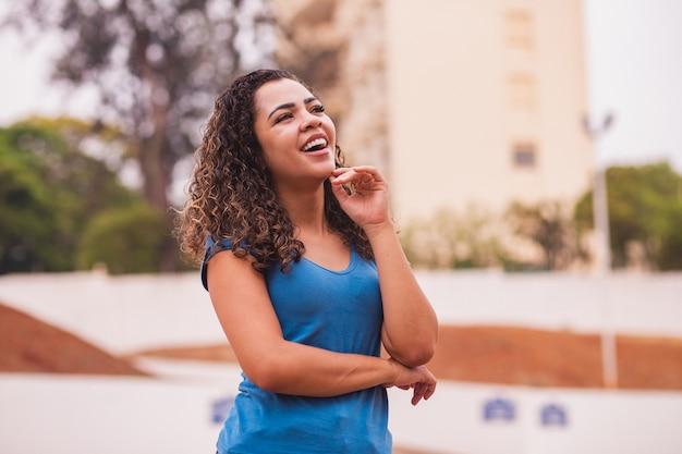 Szczęśliwa kobieta afro w aparacie. młoda kobieta afro uśmiechnięta