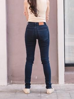 Szczęśliwa kobieta asia w dżinsowe chude jeansy, niebieskie dżinsy midnight, widok z tyłu