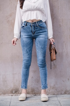 Szczęśliwa kobieta asia w jasnoniebieskich chudych dżinsach, błękitne dżinsy