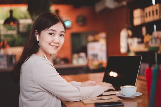 Szczęśliwa kobieta azji koncentruje się na pracy w kawiarni przy użyciu komputera przenośnego. pewna azjatka używa komputera przenośnego do przeglądania internetu i sieci społecznościowych z pięknym uśmiechem.