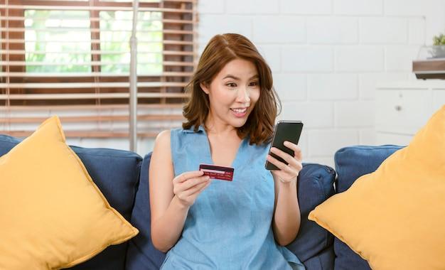 Szczęśliwa kobieta azji relaks na wygodnej kanapie za pomocą smartfona i karty kredytowej zakupy online w domu w salonie.