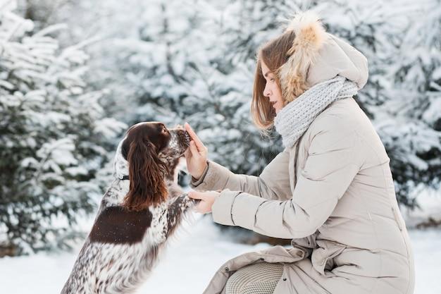 Szczęśliwa kobieta bawi się czekoladowym spanielem w zimowym lesie. ścieśniać.