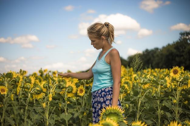 Szczęśliwa kobieta bawi się słonecznikiem na świeżym powietrzu dziewczyna bawi się w zielonym wiosennym polu