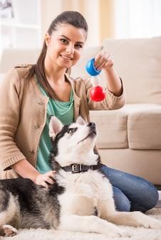 Szczęśliwa kobieta bawi się z psem w domu.
