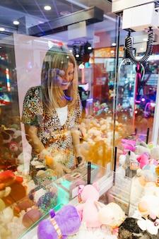 Szczęśliwa kobieta bawić się arkadową maszynę