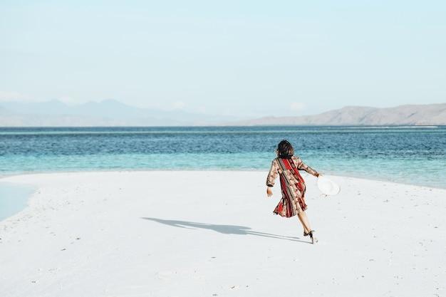 Szczęśliwa kobieta biegająca i tańcząca na białej, piaszczystej plaży