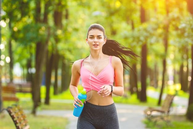 Szczęśliwa kobieta biegająca po parku