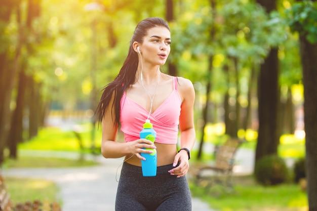 Szczęśliwa kobieta biegająca w parku na słonecznym tle