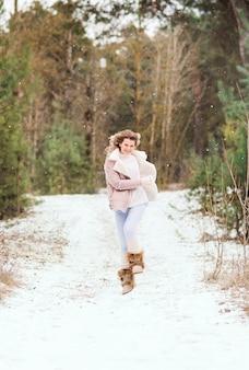 Szczęśliwa kobieta biegnie i skacze w zimowym lesie. ma na sobie lekkie ubrania.