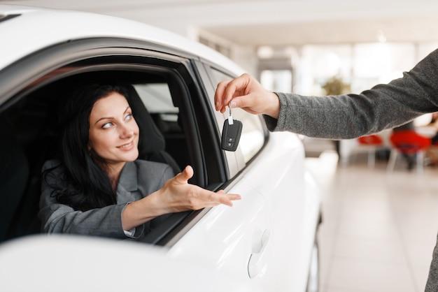Szczęśliwa kobieta bierze klucz do nowego samochodu w salonie.