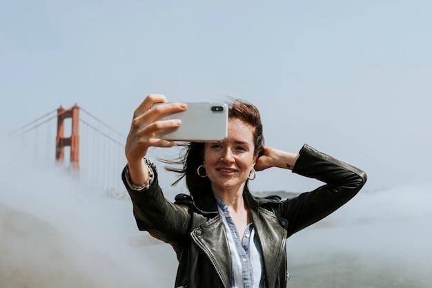 Szczęśliwa kobieta bierze selfie z golden gate bridge, san fransisco
