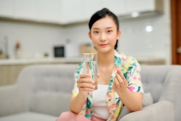 Szczęśliwa kobieta biorąc witaminę żółtą pigułkę siedząc na kanapie w salonie w domu