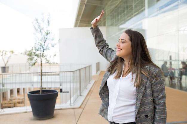 Szczęśliwa kobieta biznesu powitanie kogoś na zewnątrz
