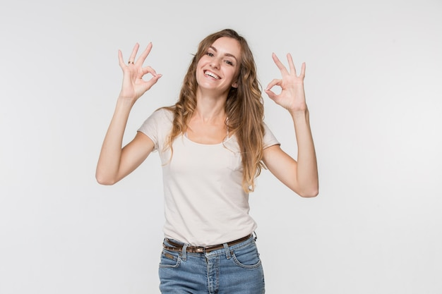 Szczęśliwa kobieta biznesu stojąc i uśmiechając się przeciw białej ścianie