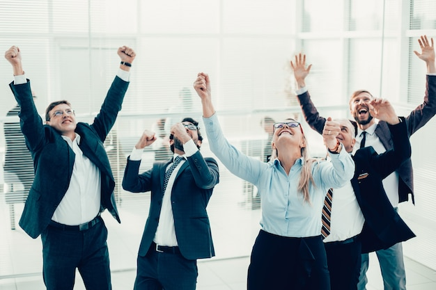 Szczęśliwa kobieta biznesu stojąca przed dopingującym zespołem biznesowym business
