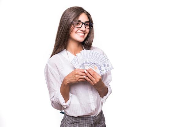 Szczęśliwa kobieta biznesu z długimi brązowymi włosami w ubranie posiada mnóstwo banknotów dolarowych na białym