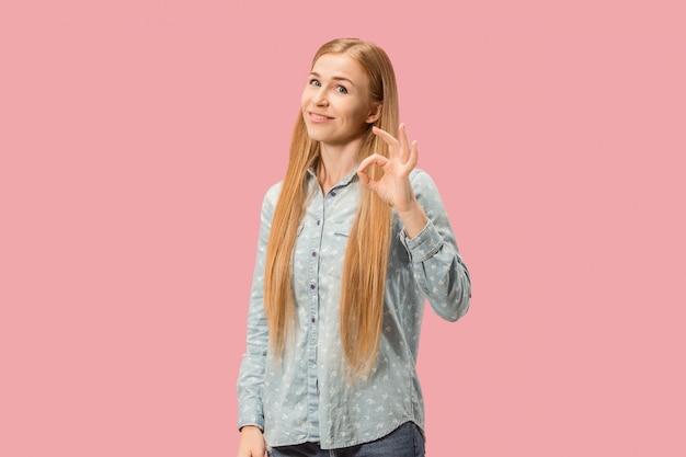 Szczęśliwa kobieta biznesu, znak ok, uśmiechnięta, na białym tle na modnym różowym studio