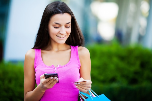 Szczęśliwa kobieta blisko zakupy centrum handlowego mienia prezenta torby