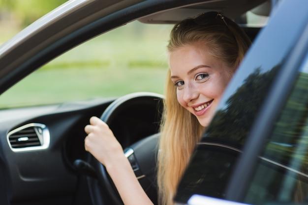 Szczęśliwa kobieta blondy jazdy samochodem