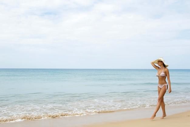 Szczęśliwa kobieta chodzi na wybrzeżu morza