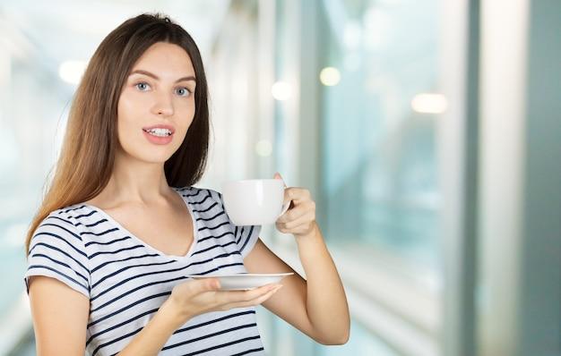Szczęśliwa kobieta cieszy się ciepłą filiżankę herbata lub kawa na śniadanie
