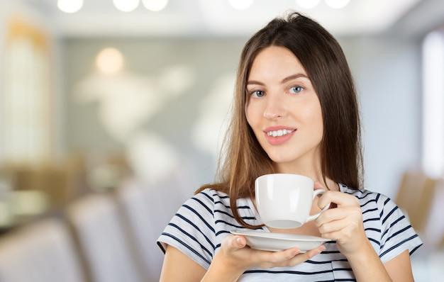Szczęśliwa kobieta cieszy się ciepłą filiżankę herbata