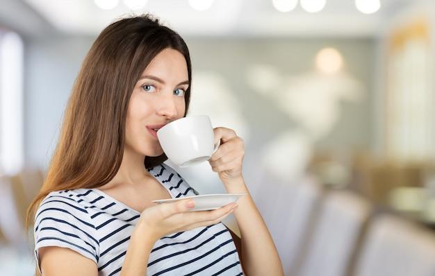 Szczęśliwa kobieta cieszy się ciepłą filiżankę herbaty lub kawy na śniadanie