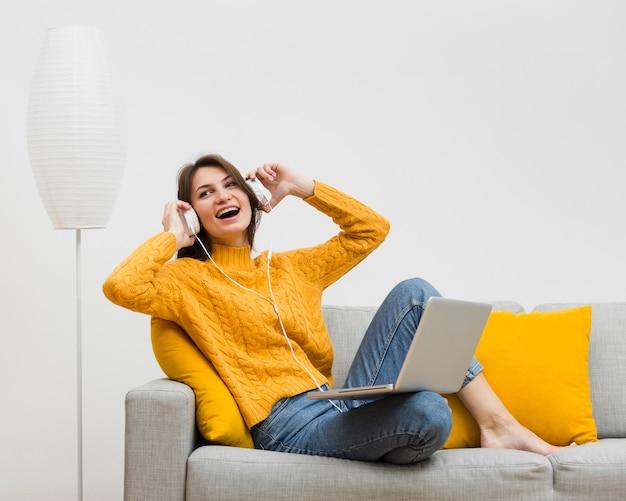 Szczęśliwa kobieta cieszy się jej muzykę na hełmofonach